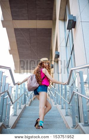 Beautiful young woman standing on steps. Slim body red-haired curly student girl relaxing at city view. Fashion model wearing trendy clothes. Beauty lifestyle concept