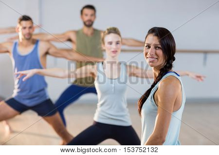 Instructor smiling at camera while students performing stretching exercise in fitness studio