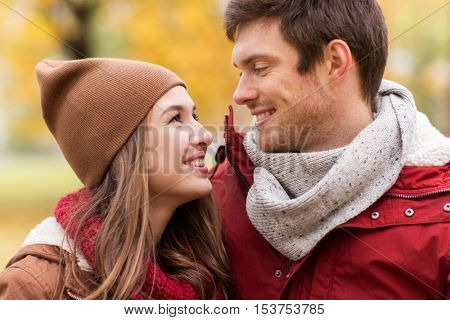 love, relationships, season and people concept - close up of happy young couple walking in autumn park and talking