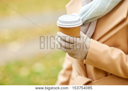 season, hot drinks and people concept - close up of woman with coffee or tea disposable paper cup in autumn park