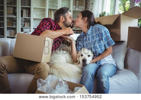 Young couple kissing each other while unpacking carton boxes in new house