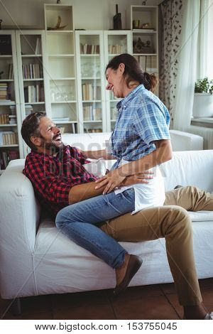 Happy woman sitting on mans lap in living room at home