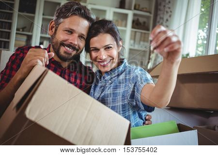Smiling couple holding keys in their new house while unpacking carton boxes