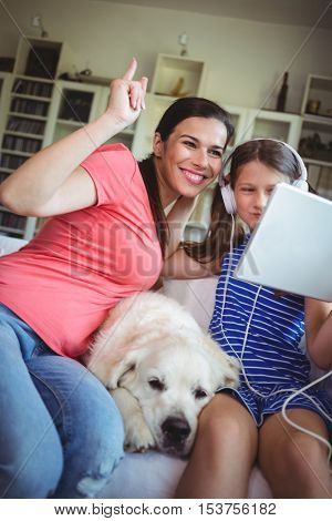 Happy mother and daughter sitting with pet dog and using digital at home