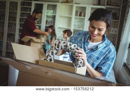 Woman unpacking cartons in the new house while family standing in background