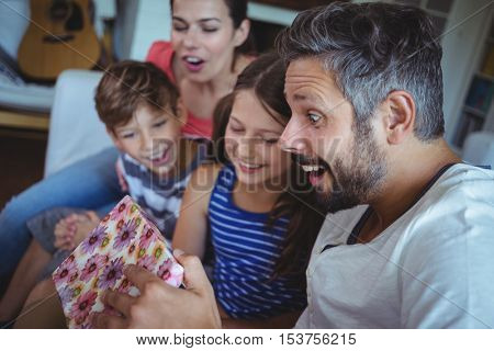 Family opening the surprise gift in living room at home