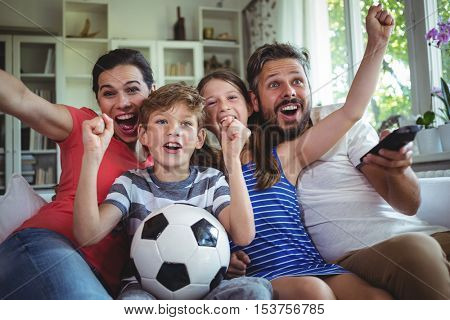 Excited family watching football match at home