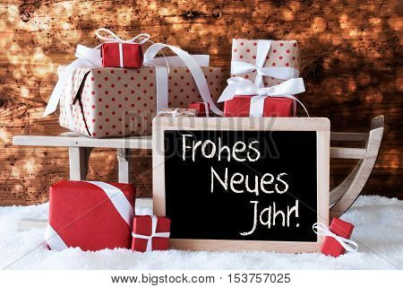 Chalkboard With German Text Frohes Neues Jahr Means Happy New Year. Sled With Christmas And Winter Decoration. Gifts And Presents On Snow With Wooden Background And Bokeh Effect.