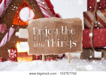 Gingerbread House In Snowy Scenery As Christmas Decoration. Sleigh With Christmas Gifts Or Presents And Snowflakes. Label With English Quote Enjoy The Little Things
