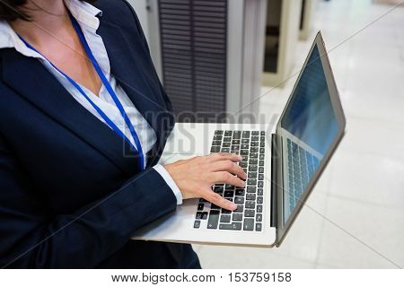 Mid section of technician working on laptop in server room