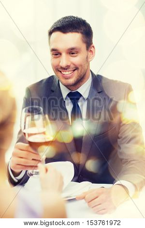 restaurant, couple and holiday concept - smiling young man with glass of red wine looking at girlfriend or wife at restaurant
