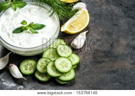 Tzatziki sauce with ingredients cucumber garlic dill lemon mint on grungy background. Healthy food