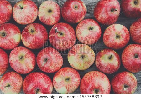 Sweet fresh ripe red apples heap scattered on gray weathered wood closeup, fruit backround. Healthy food on table, top view. Fall harvest, farming agricultural concept