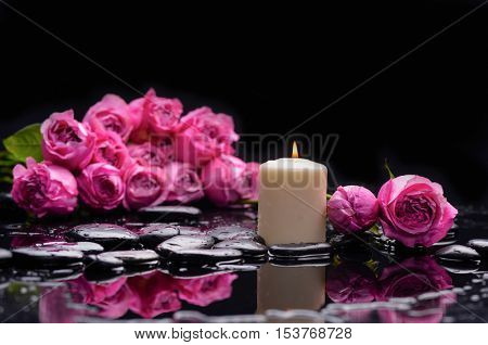 Lying down branch rose with candle and therapy stones