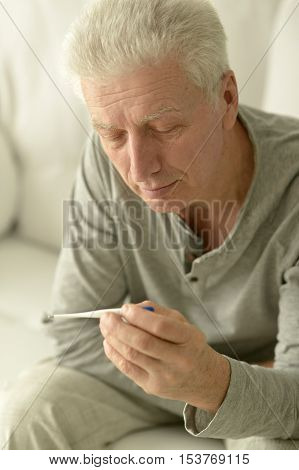 portrait of Sick mature man with thermometer