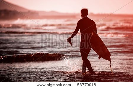 Silhouette of man with a surfboard on the beach