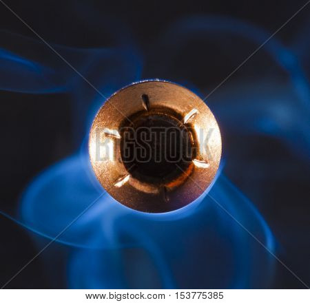 Hollow point copper jacketed bullet and smoke on a dark background