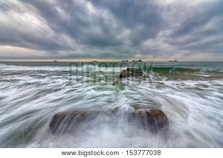 Beauty cloudy, long exposure seascape with slow shutter and waves flowing out.