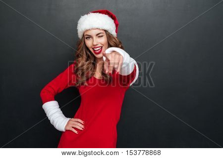 Beautiful woman in santa's costume shows a finger at the camera