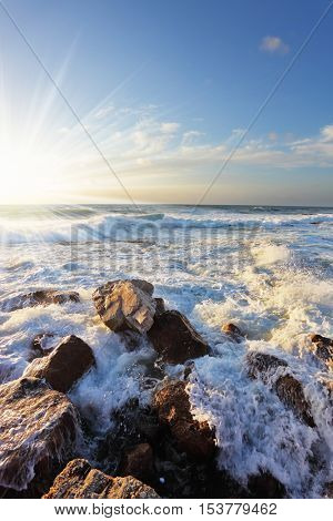 Gorgeous sunset on the Mediterranean. Storm waves crash on the breakwater at the quay. Tel Aviv, the spring