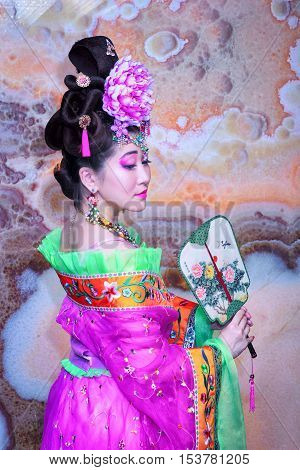 Asian woman with Chinese traditional dress cheongsam or qipao holding Chinese fan. Chinese new year concept female model