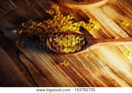 Round small fish oil capsules on wooden spoon scattered on a wooden surface