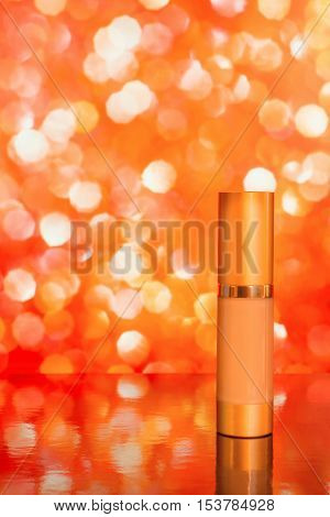 Golden cosmetic tube of tinted cream on bright red blurred background with reflection. Copy space included