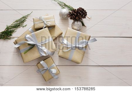 Top view of Gift boxes on white wood background. Presents wrapped in paper with elegant silver satin ribbon bows, decorated with fir tree and pine cones. Christmas holidays concept, copy space.