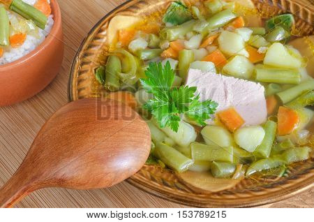 Soup of pork with vegetables and rice, a ceramic bowl and a wooden spoon. Stands on table, close-up.