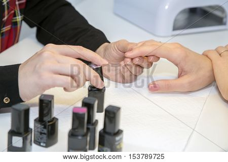 Manicurist doing manicure client painting nails with polish in salon