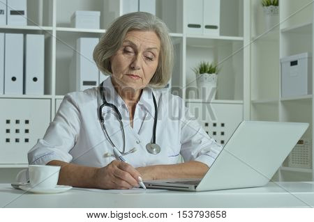 happy senior doctor sitting at table with laptop in office
