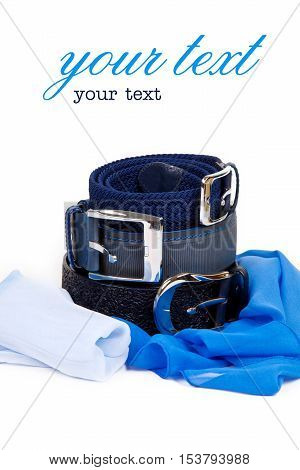 Three leather belt in a row on top of each other on a white background with a metallic blue silk scarf female buckles. Clothing accessories