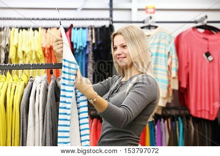 Smile woman in the clothing shop. Girl in clothes store