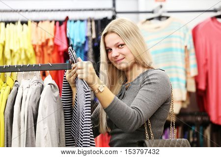 Happy woman in clothing shop. Girl in clothes shop