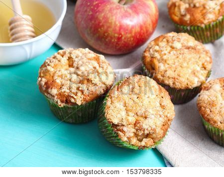 Apple crumb spiced muffins with streusel topping on green pastel wooden table with napkin and honey