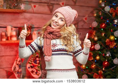 Blonde woman in warm sweater with thumbs up near decorated Christmas tree. Smiling young blond female showing ok gesture