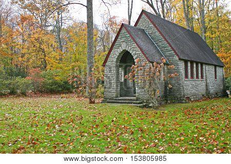 a small stone chapel sits amid colorful autumn foliage