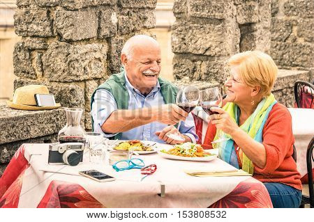 Senior couple having fun and eating at restaurant during travel - Mature man and woman wife in old city town bar during active elderly vacation - Happy retirement concept with retired people together