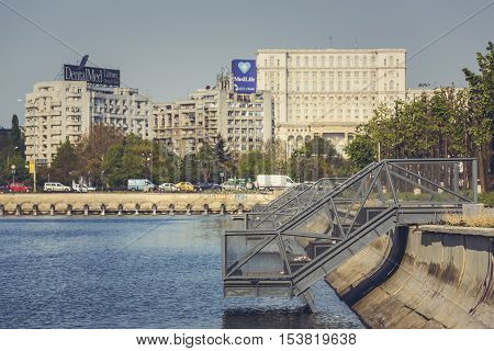 Bucharest Romania - April 14 2014: Sunny cityscape with metallic piers on Dambovita riverbank near the Union Square (Piata Unirii) and the Palace of the Parliament also known as People's House.