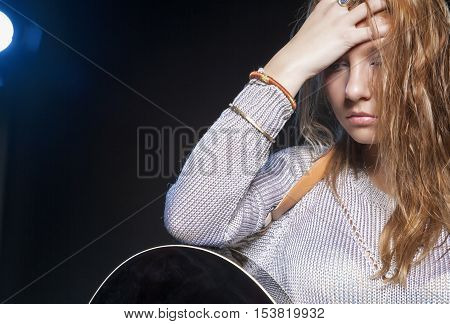 Music Concept and Ideas. Young Blond Female Posing with Guitar Against Black. Horizontal Image Orientation