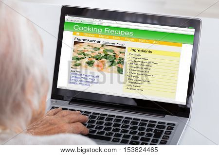 Close-up Of Senior Woman Using Laptop For Learning Recipe On Website At Home