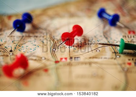 Close-up of several color pushpin on a geographic map. The choice of the route.