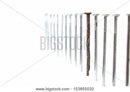 Row of the new nails with one old and rusty between them. Weak point metaphor