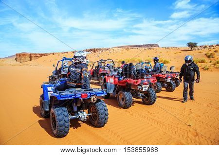 Merzouga Morocco - Feb 26 2016: back view on group of off-road pilots during a break in Morocco desert near Merzouga. Merzouga is famous for its dunes the highest in Morocco.