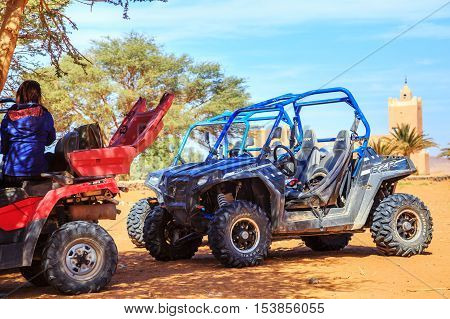 Merzouga Morocco - Feb 26 2016: back view on an off-road pilot during a break in berber village on Morocco desert near Merzouga. Merzouga is famous for its dunes the highest in Morocco.