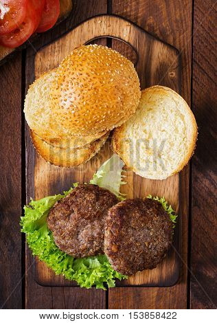 Ingredients For A Sandwich - Hamburger Burger With Beef, Pickles, Tomato And Red Onion On Wooden Bac