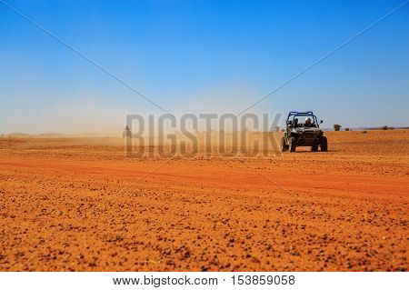 Merzouga Morocco - Feb 23 2016: Side view on blue Polaris RZR 800 with it's pilots in Morocco desert near Merzouga. Merzouga is famous for its dunes the highest in Morocco.