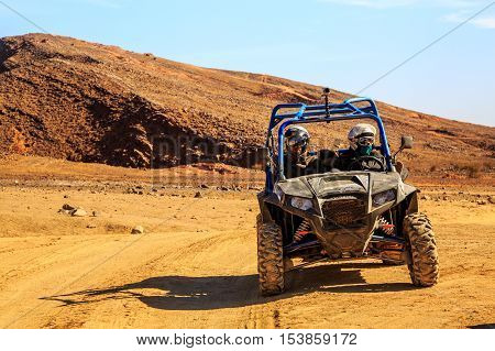 Merzouga Morocco - Feb 26 2016: front view on blue Polaris RZR 800 with it's pilots in Morocco desert near Merzouga. Merzouga is famous for its dunes the highest in Morocco.