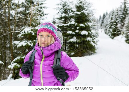 Woman hiking in white winter forest woods with backpack. Young girl walking on snowy trail. Recreation fitness and healthy lifestyle camping outdoors. Motivation and inspirational winter landscape.