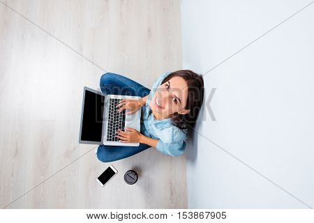 Pretty Happy Woman Sitting On Floor With Laptop, Top View Photo